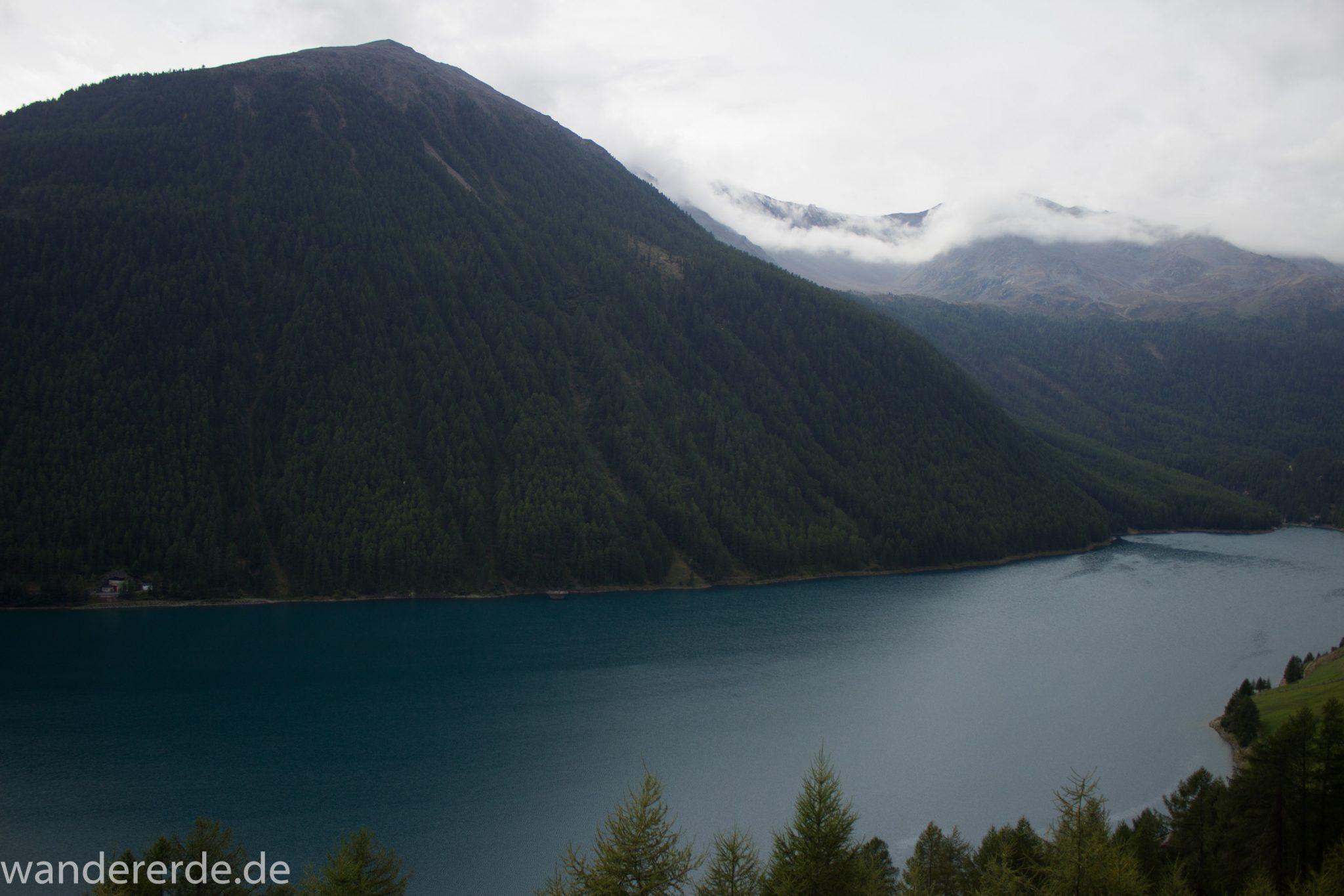 Alpenüberquerung Fernwanderweg E5 Oberstdorf Meran, 6. Etappe von Martin-Busch-Hütte nach Vernagt / Meran, nach dem Aufstieg zur Similaun-Hütte auf der letzten Etappe der Alpenüberquerung auf dem E5 verläuft der Wanderweg steil abwärts Richtung Vernagt im Schnalstal,  Blick auf den Stausee in Vernagt und die umliegenden Wälder, saftig grüne Vegetation, Stausee ist das Ziel der Alpenüberquerung auf dem E5, nach Meran geht es weiter mit dem Bus und Zug